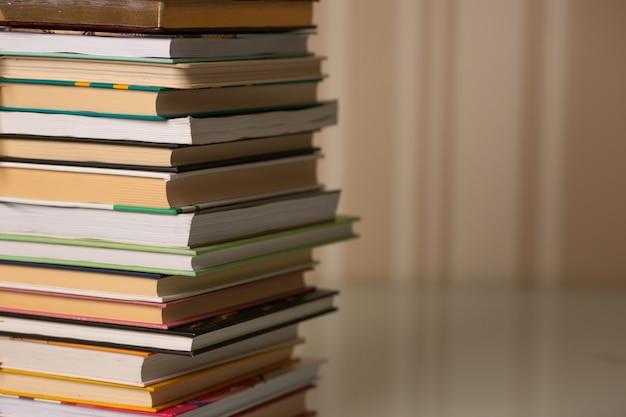 집 근접 촬영에서 책상에 책의 스택. 베이지색 줄무늬 배경입니다. 텍스트를 위한 공간
