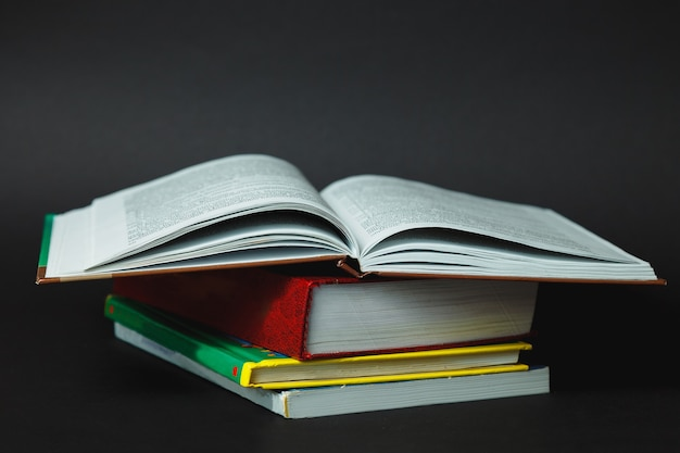 黒の背景に本のスタック。本の山