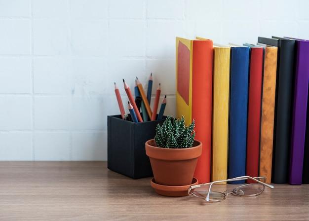 Стопка книг на рабочем столе. различные книги и канцелярские товары на столе