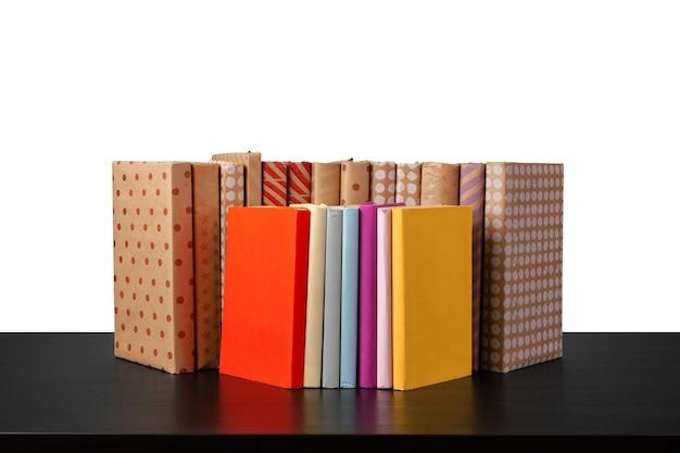 흰색 배경에 대해 나무 테이블에 책의 스택