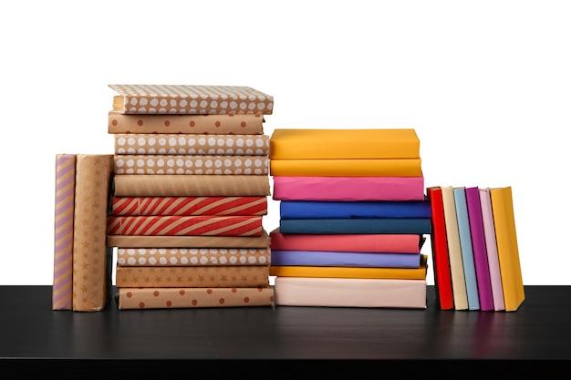 Стопка книг на деревянном столе на белом фоне