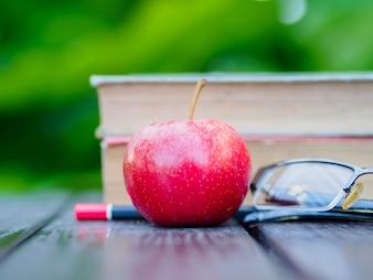 木製のテーブルに本、鉛筆、ガラス、赤いリンゴのスタック。