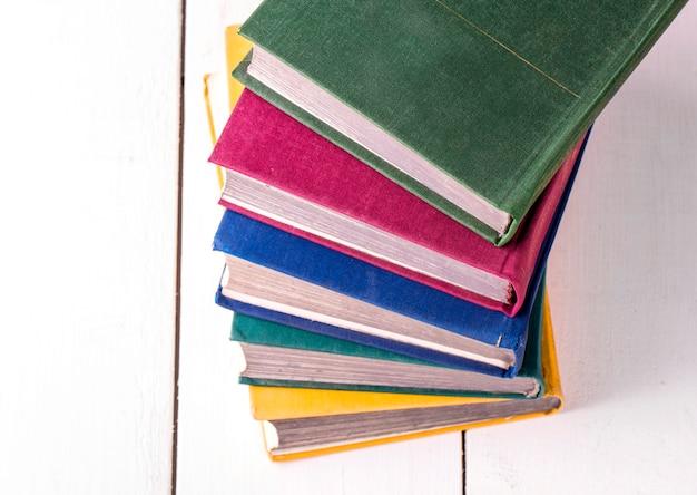 本のスタックは、白い木製のテーブルのクローズアップを撮影しました