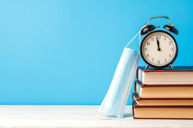 알람 시계와 책상에 의료 마스크 책의 스택