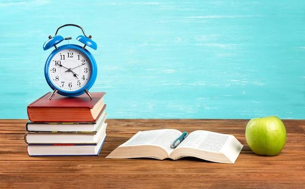 나무 책상에 알람 시계와 함께 서의 스택.