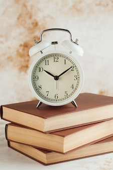 目覚まし時計が付いている本のスタック。読書、勉強、宿題、教育の概念に集中する時間。