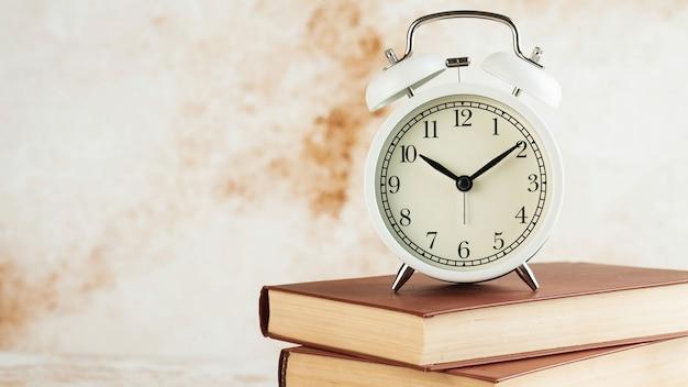 目覚まし時計が付いている本のスタック。読書や勉強や教育の概念に集中する時間。コピースペース