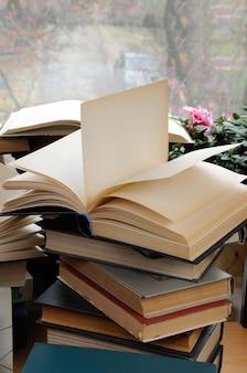 클로즈업 위에 펼친 책이 있는 책 더미