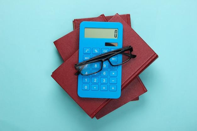 Стопка книг с калькулятором на синем