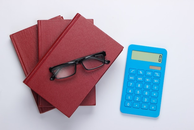 Стопка книг с калькулятором на белом