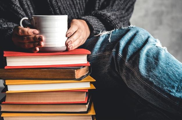 本、教育、トレーニング、趣味を読んでいる女性の前にマグカップが上にある本のスタック