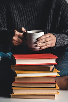 本を読んでいる女性の前にマグカップが上にある本のスタック