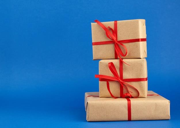 Стек коробки, завернутые в коричневую бумагу и перевязанный красным бантом, подарки на синем фоне