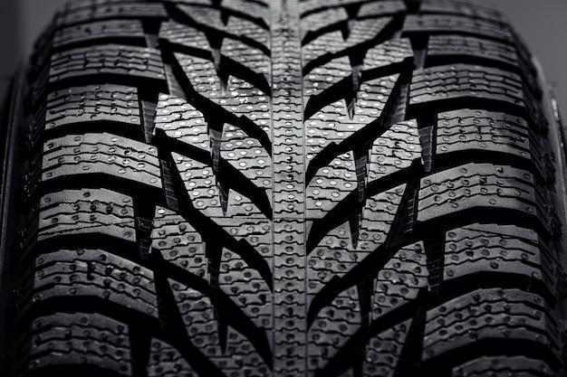 きれいなハイキー白いスタジオの壁に真新しい高性能車のタイヤのスタック。新しい車のタイヤの壁。テクスチャのクローズアップ