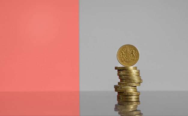Стек британских фунтов на современном сером фоне, одна монета, сбалансированная наверху.