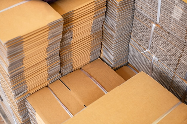 Стопка коричневых сложенных картонных коробок, связанных для упаковки