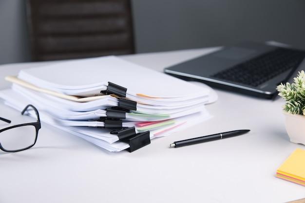 Стек деловой бумажный файл с портативным компьютером на столе