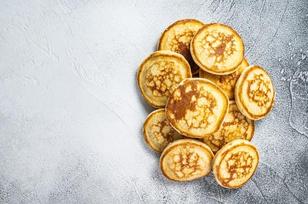 台所のテーブルにバターを塗ったパンケーキのスタック。白色の背景。上面図。スペースをコピーします。