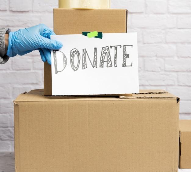 段ボール箱のスタックと碑文と白い紙のシートは、白いレンガの壁の背景に寄付します