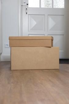 Стопка пустых картонных коробок в прихожей нового дома на этаже переезда хранения или доставки