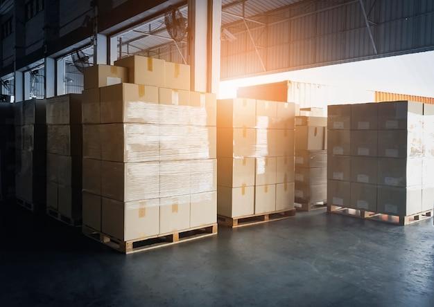Стек картонных коробок в ожидании загрузки в грузовой контейнер. грузовые перевозки, отгрузка, доставка складских услуг.
