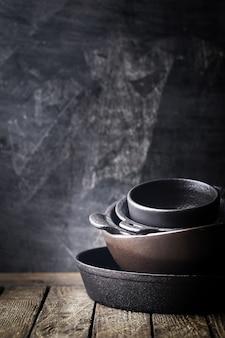 暗闇の上の鋳鉄調理器具のスタック