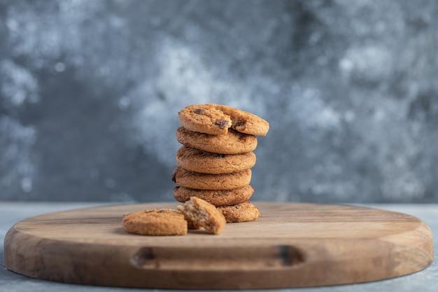 Стек шоколадного печенья на деревянной доске.