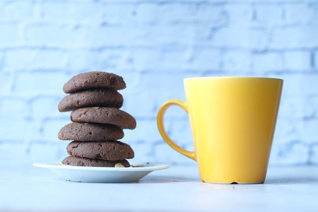 テーブルの上のチョコレートクッキーとコーヒーマグのスタック