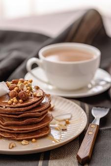 Стек шоколадных блинов с кленовым сиропом, медом и чашкой кофе, хорошая закуска, вертикальная