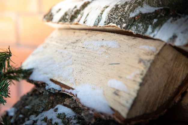 雪の中で刻んだ薪のスタック冬の薪の準備。