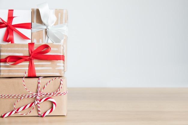 빨간색, 흰색 리본, 테이블에 사탕 지팡이와 공예 종이에 크리스마스 선물 상자 스택. 흰색 배경, 여유 공간.