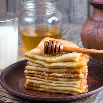 Стек классических блинов с медом на тарелке