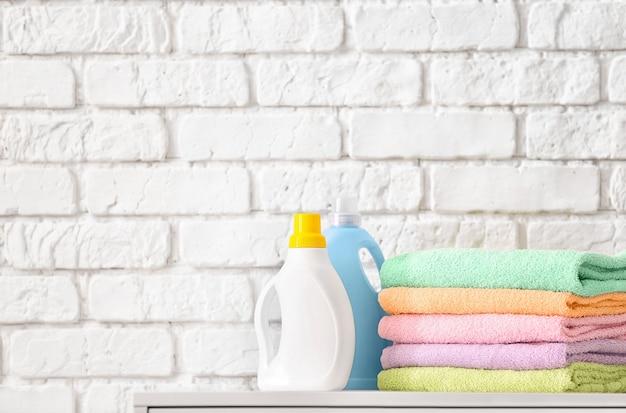 벽돌 벽 근처 테이블에 깨끗한 수건과 세탁 세제의 스택