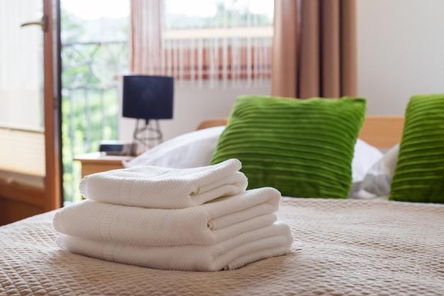 Стек чистых белых полотенец на кровати. хлопковое мягкое белое полотенце в отеле