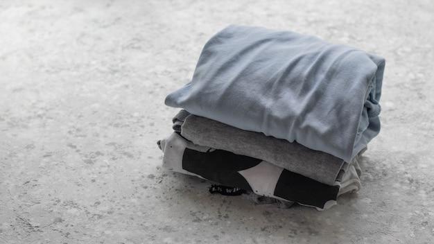 コピースペースでコンクリートの背景に折り畳まれた服のスタック