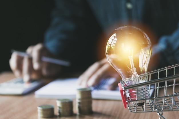 Стек монет и лампочек в корзине покупок для учета и бизнес-концепции.