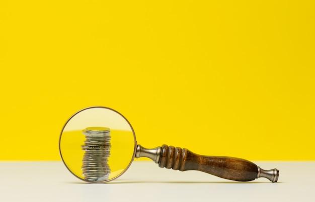 コインのスタックと白いテーブル、黄色の背景に木製の拡大鏡。予算資金の分析、支出と収入の管理の概念。少額の給与、スタートアップのための資金調達