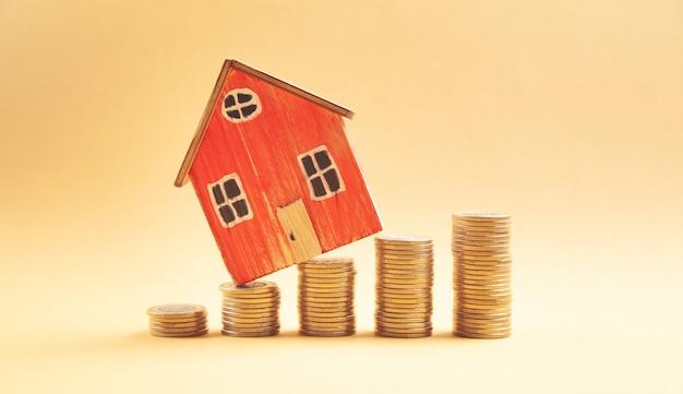 コインのスタックと家のモデル。家を買うためのお金を節約する