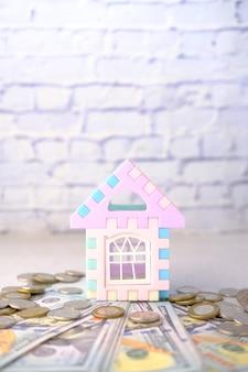 コインのスタックとテーブル上の家ハウスファイナンスの概念