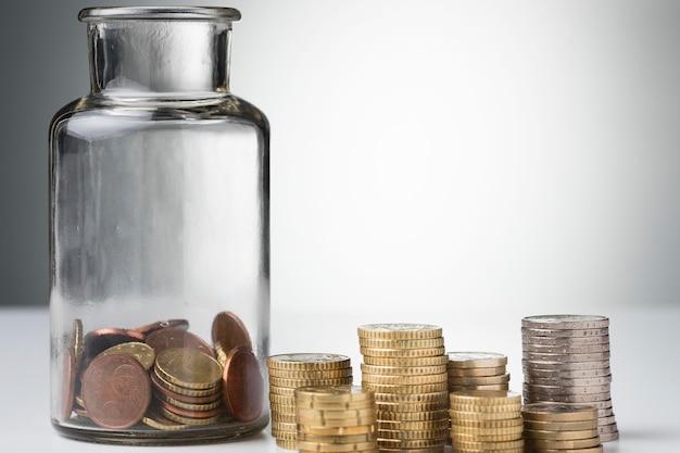 Стопка монет и банка