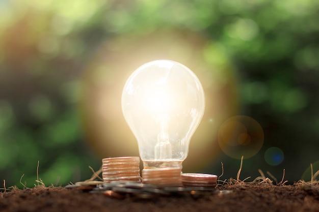 전구 에너지 절약 개념을 가진 동전과 돈의 스택. 저축, 회계 및 금융 개념입니다.