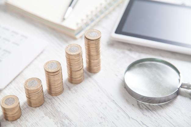 コインのスタック、虫眼鏡、タブレット、電卓。