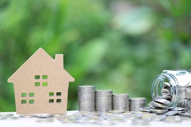 Стопка монет денег и модель дома на естественном зеленом фоне