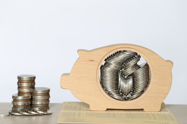 Стог денег монеток в древесине копилки на белой предпосылке, сохраняя деньги для подготовки в будущем и концепция вклада