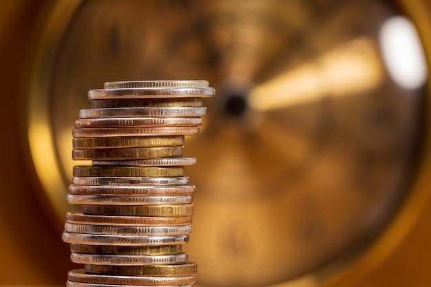 시계 배경에 동전의 스택. 돈 시간 개념