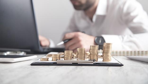 机の上のコインのスタック。ラップトップで作業するビジネスマン