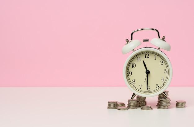 テーブルの上の白い目覚まし時計の周りのコインのスタック。時間の概念はお金、割引の期間です。