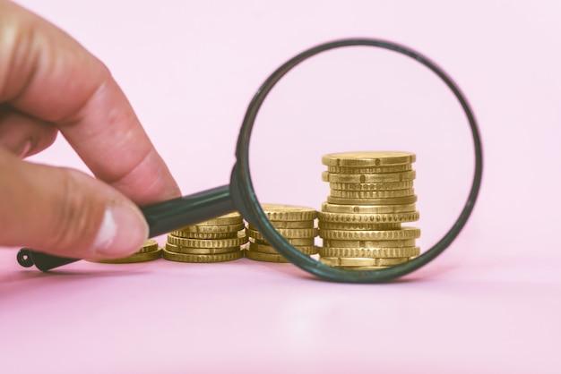 ピンクの背景に拡大鏡を介してコインのスタック。ユーロ硬貨。