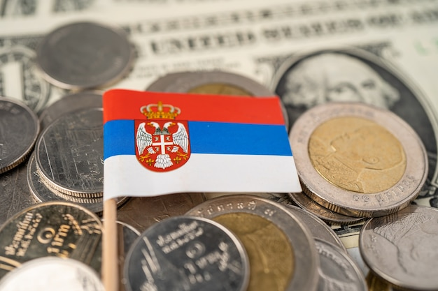 미국 달러 지폐에 세르비아 국기가 있는 동전 더미.