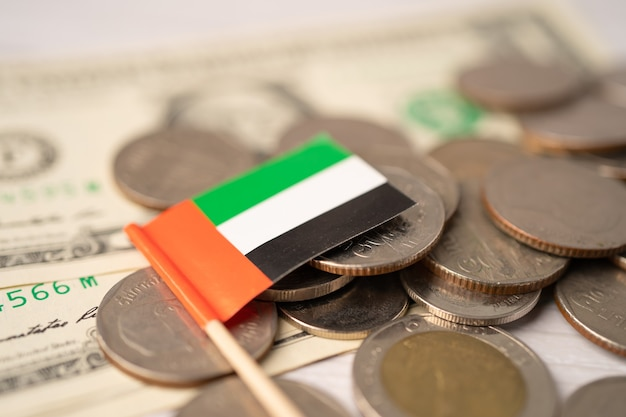 Стек монет с флагом объединенных арабских эмиратов оаэ.